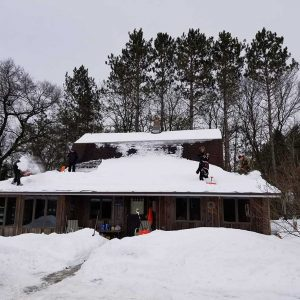 Shoveling snow of the roof.