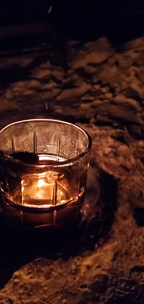 A campfire reflection in a glass of whiskey
